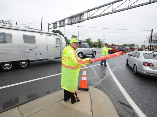 Bob Yerkes, left Houston Fire Police and Tim Weishaupt with DelDOT help direct traffic of Firefly fans on Leipsic Road to enter the camping area at the 2015 Firefly Music Festival.