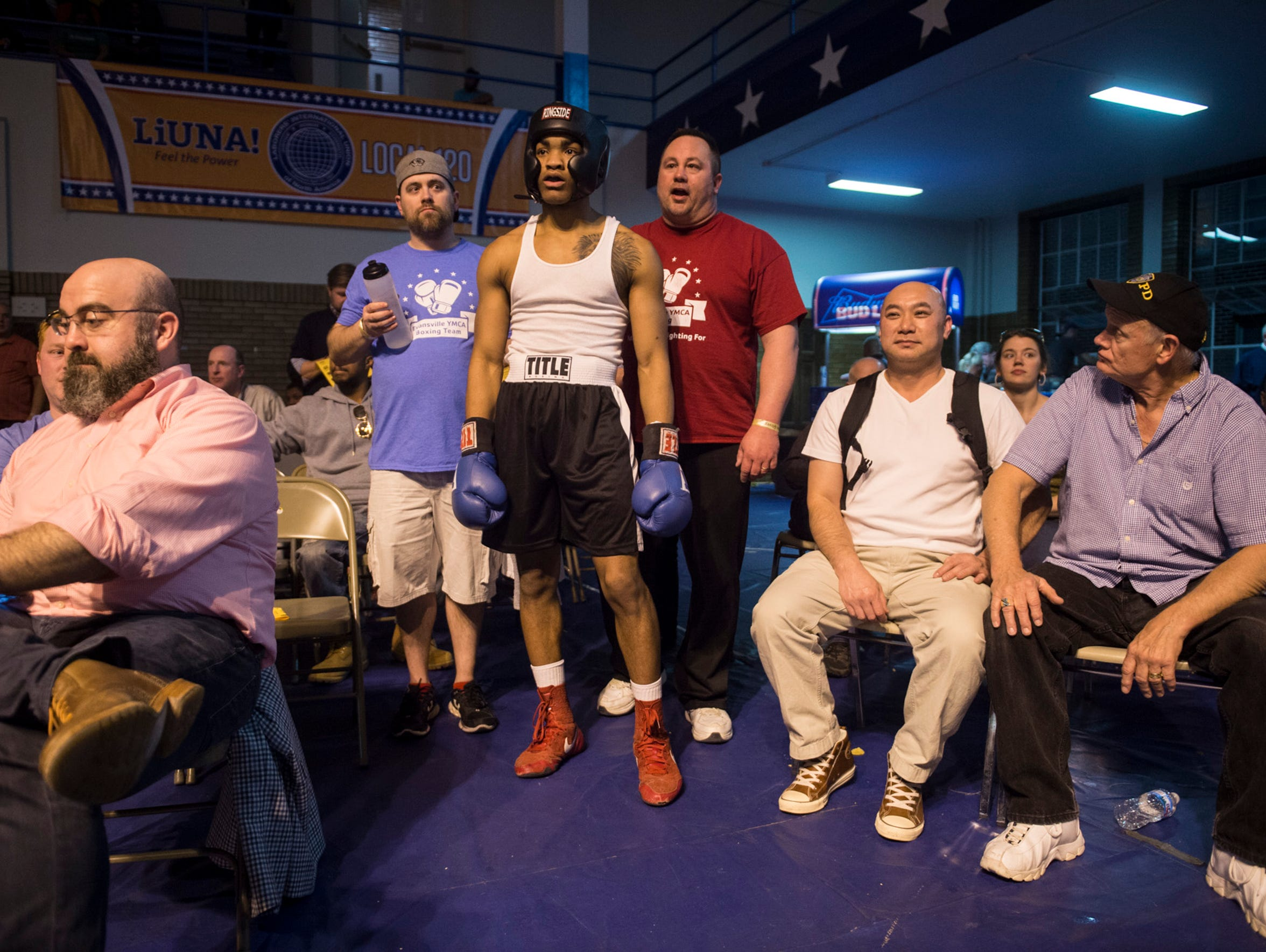 Raymon Henry, middle, stands just outside the ring