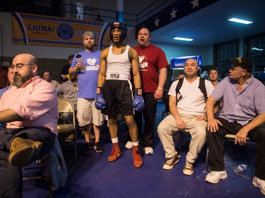 Raymon Henry, middle, stands just outside the ring as he awaits his fight during the Indiana State Golden Gloves regional semi-championship at the Tyndall Armory in Indianapolis on Thursday, April 12, 2018.