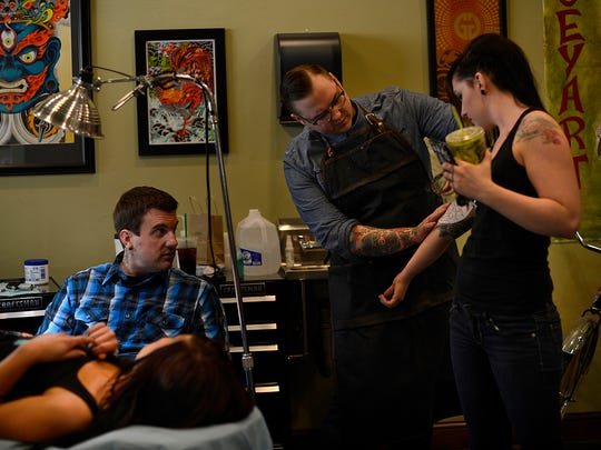 At left, Paul Dhuey gives some advice to artist Micah Gunderson on the placement of a tattoo to Paige Bergman, 23, of De Pere, inside Katana Tattoo studio in Green Bay on Monday, May 5, 2014. Also shown is Alissa Sieloff, 27, of Green Bay. Evan Siegle/Press-Gazette Media
