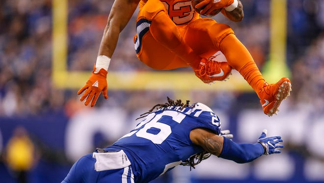 Indianapolis Colts free safety Clayton Geathers (26) is leaped over by Denver Broncos running back Devontae Booker (23) at Lucas Oil Stadium in Indianapolis on Thursday, Dec. 14, 2017. Booker would find the end zone but a penalty against the Broncos would negate the touchdown.