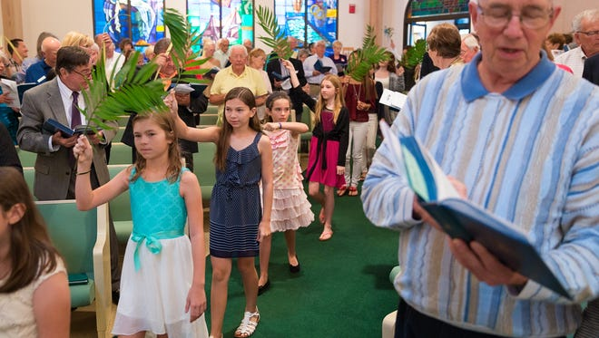 Children from Vanderbilt Presbyterian Church process through a Palm Sunday service waving palm tree fronds on Sunday, March 29, 2015, in North Naples. The congregation is hoping to be back in its church with wider aisles and a brand-new pipe organ for the coming Easter.