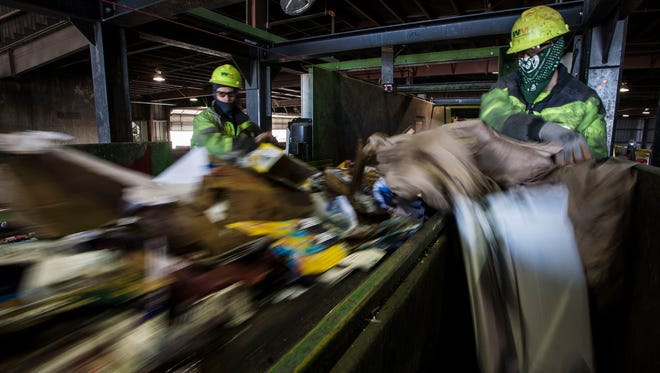 Material sorters Triston Hamilton, right, and Levi Johnson  pick materials not suitable for recycling off a conveyer belt on Tuesday, April 3, 2018, at the Larimer County Recycling Center on the South edge of Fort Collins, Colo.
