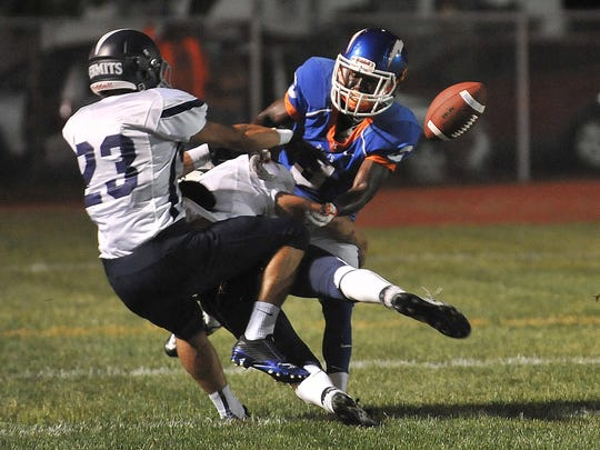 A pass to Millville's Dajour Brown (3), is broken up by St. Augustine's Sean Mulhern (23) and Andrew Baxter (4), Friday, Sep. 18, 2015 in Millville.