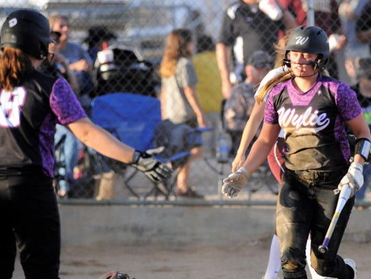 Wylie's Lilly New (16) gets a high-five from Kaylee Beard (18) after scoring in the fourth inning of the Lady Bulldogs' 4-3 loss to Vernon on Friday.