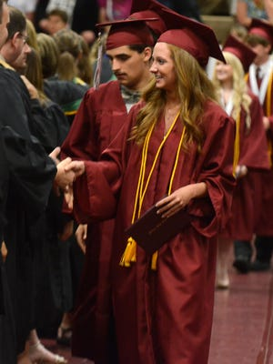 Milford High class of 2016 graduates shake hands with members of the school's faculty. Officials from multiple area districts are trying to plan for a more traditional ceremony as we near the second graduation season in a pandemic.