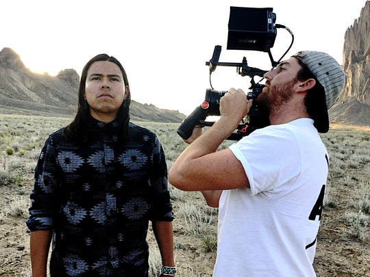 "Director Kody Dayish is featured with cinematographer Tyler Hast on the set of the film ""The Red Hogan"" during a shoot at the Shiprock pinnacle."