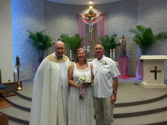Fr. Kris Bauta (left) stands with Donata and John Morris