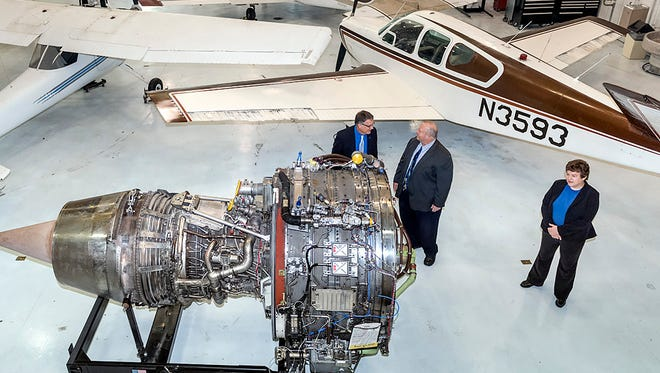 From leftt, MTSU Interim Provost Mark Byrnes, Bud Fischer, dean of the College of Basic and Applied Sciences, and Wendy Beckman, interim chair of the Department of Aerospace, inspect a recently donated engine from Southwest Airlines to help train students. The engine was unveiled Tuesday inside the MTSU Flight Operations Center maintenance hangar at Murfreesboro Airport.
