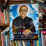 A portrait of Roman Catholic Archbishop Oscar Romero decorates a used book stand near the Metropolitan Cathedral in San Salvador, El Salvador.