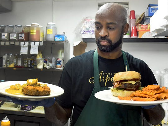 Owner Thurman Johnson holding dishes served at Arpeggios Lounge and Event center for lunch