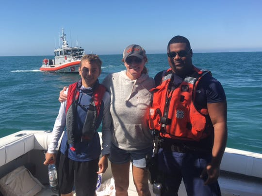 A Coast Guard officer standss with Cheryl Casabona and her son Jake, 12, aboard their boat the Irish Lady on Saturday, Feb. 4, 2017. The Casabona family helped rescue five people, including three children, from a capsized boat 12 miles west of Gordon Pass.