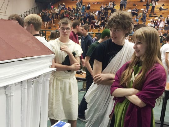 Students admire a model Roman temple on display Friday