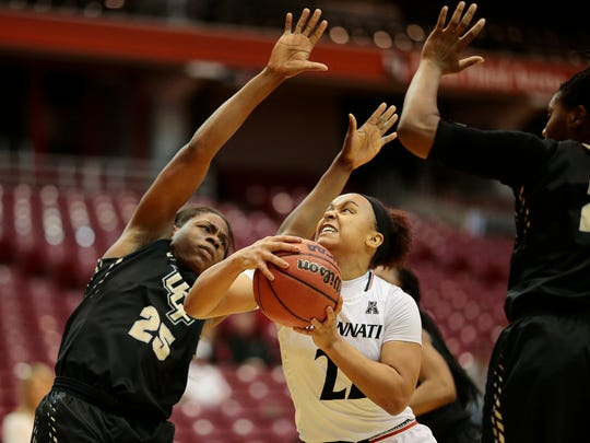 Cincinnati Bearcats guard Bianca Quisenberry (22) drives to the hoop against UCF Knights forward Tolulope Omokore (25) in the first quarter of the NCAA women's basketball game between the Cincinnati Bearcats and the UCF Knights at Fifth Third Arena on UC's campus in Cincinnati on Wednesday, Jan. 4, 2017. At the half, the Bearcats led 30-25 in the conference matchup.