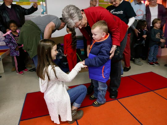 Avery Winn, 9, and Donna King, volunteers with Seminole Baptist Temple, get a high-five from Dustin Rogers, 4, while distributing over 300 winter coats to students at Cowden Elementary School on Friday, Nov. 18, 2016.