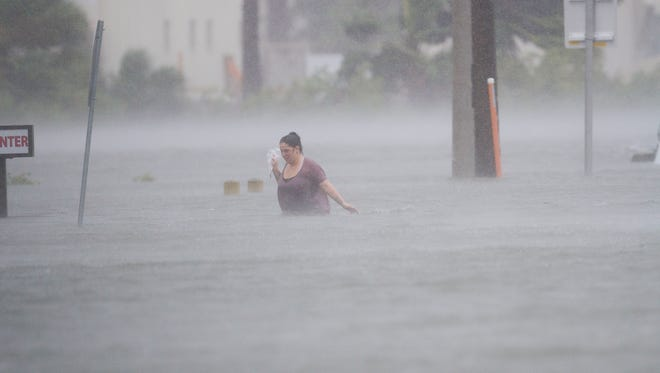 An unidentified woman makes her way through a flooded street in St. Augustine, Fla., on Oct 7, 2016.  Hurricane Matthew skirted the area causing major flooding, especially in downtown St. Augustine.