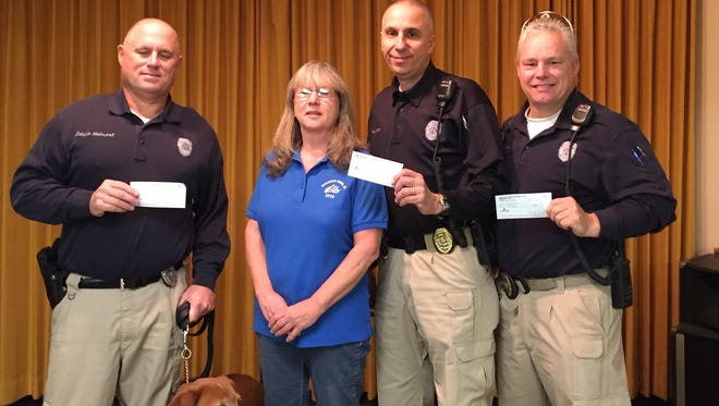 "The Mountain Elks Lodge 1714 recently presented checks for a total of $900 to the Mountain Home Police Department School Resource Officer Program. School Resource Officers are responsible for providing students a safe learning environment, and promoting positive relations between youth and law enforcement. Shown are Officer Eddie Helmert,from left; Bomber, SRO drug dog; Lisa Houser, Elks Benevolence Committee chair; Sgt. Tom Canta, and Officer Chester ""Bubba"" Jones."