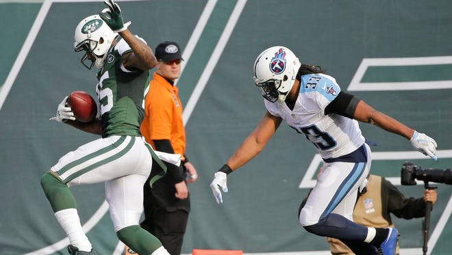 New York Jets wide receiver Brandon Marshall (15) runs past Tennessee Titans' Michael Griffin (33) for a touchdown during the first half of an NFL football game Sunday, Dec. 13, 2015, in East Rutherford, N.J.  (AP Photo/Julie Jacobson)