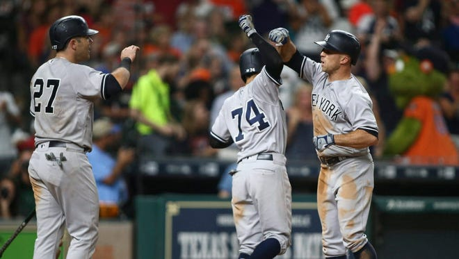New York Yankees left fielder Brett Gardner (11) celebrates with second baseman Ronald Torreyes (74) after hitting a grand slam during the seventh inning against the Houston Astros at Minute Maid Park.