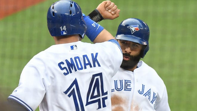 Toronto Blue Jays first baseman Justin Smoak (14) is greeted by right fielder Jose Bautista (19) after hitting a three run home run against Boston Red Sox at Rogers Centre.