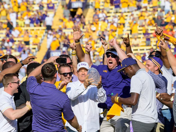 Former LSU head coach Les Miles, center, is mobbed