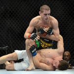 Joe Lauzon, top,  fights Mac Danzig  during  UFC on FOX  in December. He says he makes a living within UFC bonus system