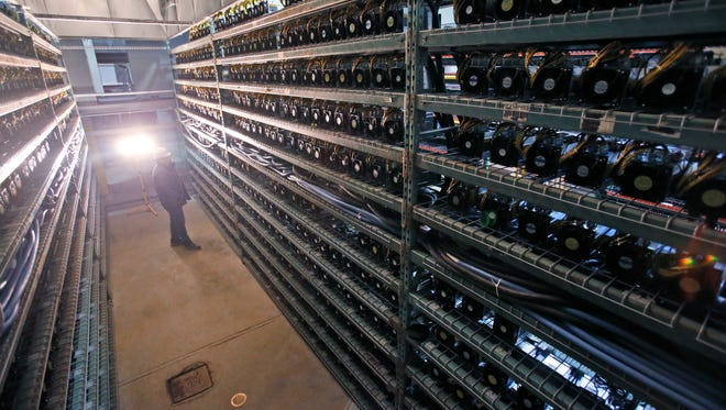 Workers look over racks of Bitcoin data miners during construction of a Bitcoin data center in Virginia Beach, Va., Friday, Feb. 9, 2018. (AP Photo/Steve Helber)