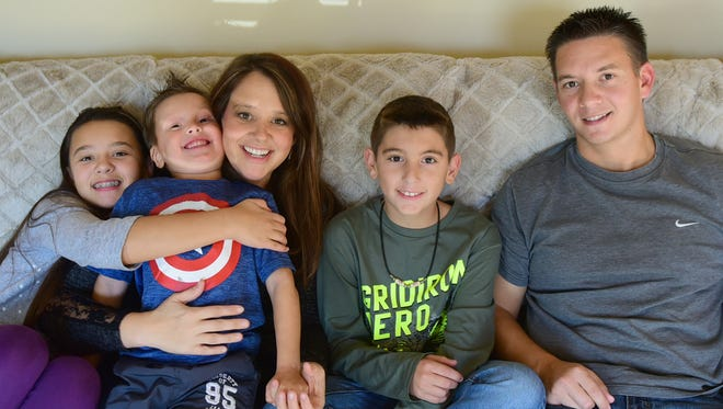Micah and Michelle Bumbaugh are pictured with their children Ava, their biological daughter, and Jameson and Christian, former foster children whom they adopted, in their Chambersburg home. Micah and Michelle have been foster parents for 11 years.