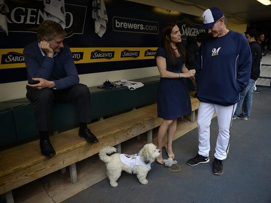 Marti Wronski, vice president of general counsel with the Milwaukee Brewers, and her dog Hank visit with Brewers manager Ron Roenicke inside the Brewers dugout before their game against the Pittsburgh Pirates at Miller Park in Milwaukee on Wednesday, May 14, 2014. Also shown is Tyler Barnes, left, vice president of communications with the Milwaukee Brewers.