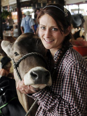 Patricia McCarthy of Clover Brook Farm in Pawling, hugs her brown Swiss cow, Cit-Cat, at the 2014 Dutchess County Fair.