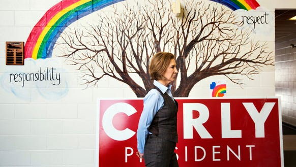 Carly Fiorina stands in front of a mural in the hallway