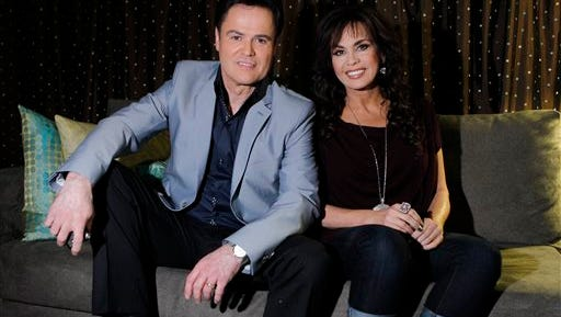 In this file photo, siblings Donny Osmond, left, and Marie Osmond pose backstage at their show at the Flamingo hotel and casino in Las Vegas. Donny and Marie Osmond will be singing at the Flamingo Las Vegas at least through the end of 2015. Caesars Entertainment Corp. announced Monday that the duo has signed on to keep performing at the hotel-casino through the end of next year.