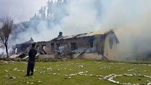 In this still image taken from video, a man watches smoke rising from an empty burning building, belonging to an army school, where a Pakistani army helicopter crashed in Nalter Valley, Gilgit,  Pakistan, Friday, May 8, 2015. The ambassadors to Pakistan from the Philippines and Norway and the wives of the ambassadors from Malaysia and Indonesia were killed Friday when a Pakistani army helicopter carrying foreign dignitaries made a crash landing in the country's north, the military said. (AP Photo)