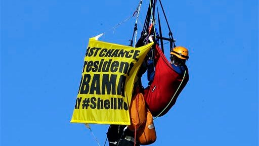 An activist hangs from the St. Johns bridge in Portland, Ore., Wednesday, July 29, 2015, to protest  the departure of Royal Dutch Shell PLC icebreaker Fennica, which is in Portland for repairs.  The icebreaker is a vital part of Shell's exploration and spill-response plan off Alaska's northwest coast.  Greenpeace officials say  the activists have enough water and food to last for days, and can hoist themselves to allow other marine traffic to pass. (AP Photo/Don Ryan)