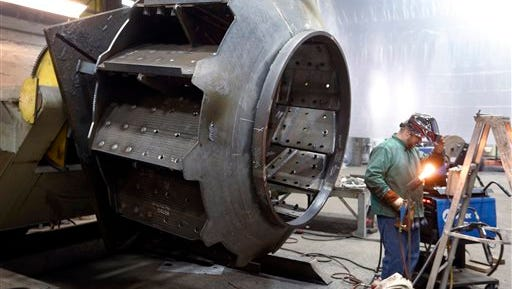 In this photo taken on Thursday, Feb. 12, 2015, a man welds parts in fans for industrial ventilation systems at the Robinson Fans Inc. plant in Harmony, Pa. After a harsh winter, the U.S. economy posted a solid rebound in the April-June quarter, led by a surge in consumer spending and a recovery in foreign trade.