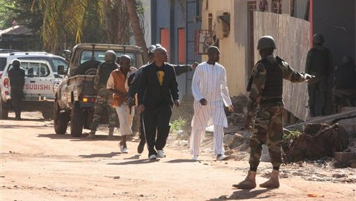 Security force personnel escort people fleeing from the Radisson Blu Hotel in Bamako, Mali, on Friday.