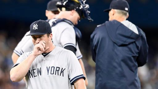New York Yankees' starting pitcher Adam Warren, bottom left, reacts after being pulled during fourth inning baseball game action against the Toronto Blue Jays in Toronto, Monday, Sept. 21, 2015. (Frank Gunn/The Canadian Press via AP) MANDATORY CREDIT