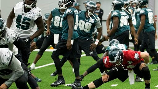 Eagles quarterback Carson Wentz (red jersey) and his teammates stretch Thursday before an indoor practice at the team's practice facility.