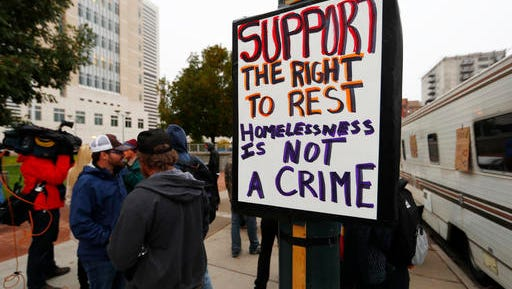 In this Wednesday, Oct. 12, 2016, photograph, a sign is affixed to a light pole during a brief rally before protesters enter the Federal Courthouse in downtown Denver for a hearing in a class action lawsuit challenging the homeless sweeps in the Mile High City last spring. The Denver lawsuit is the latest in a string of cases opposing crackdowns on people camping in public around the country. (AP Photo/David Zalubowski)