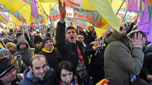 Pro-Kurdish  demonstrators protest  against Turkish president Recep Tayyip Erdogan and the political repression that followed July's failed military coup,  in Cologne, Germany Saturday, Nov. 12, 2016. People showing flags  with detained Kurdistan Workers Party, PKK , leader Abdullah Ocalan.