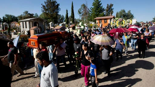 People accompany the coffin that contain the remains of Martina Almazan, a victim of the massive fireworks explosion, in Tultepec, Mexico, Thursday, Dec. 22, 2016. A downtown Tultepec Catholic church hosted funeral Masses throughout the day Thursday for victims of the massive fireworks explosion at the San Pablito Market on Tuesday, that killed more than 30 people.