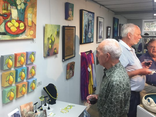 Clemson artist Joe Merck admires pieces by Pam LaTour and Lori Solymosi at Friday night's grand reopening for the Art Gallery on Pendleton Square.