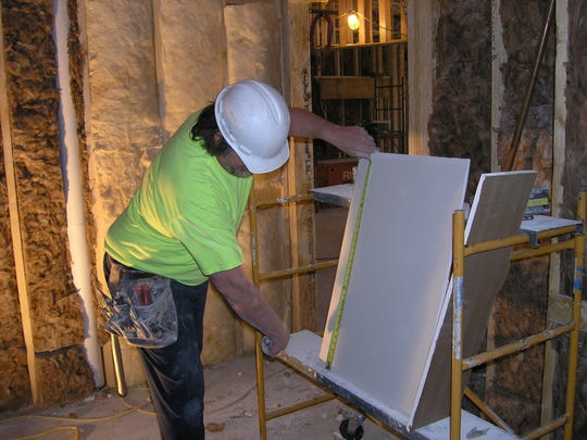 Jim Pribyl of Denkins Drywall, Kaukauna, measures a piece for Veterans Manor in Green Bay. The 50-unit apartment building is expected to open in June.