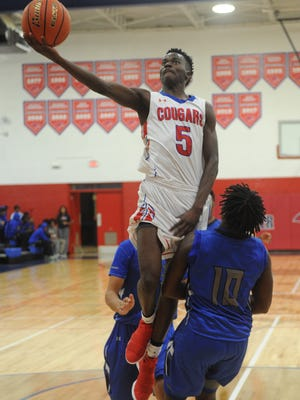 Cooper's Matthew Falade (5) drives to the basket while Lubbock Estacado's Jalen Turner defends. Estacado beat the Cougars 65-37 in the nondistrict boys basketball game Tuesday, Nov. 28, 2017 at Cougar Gym.