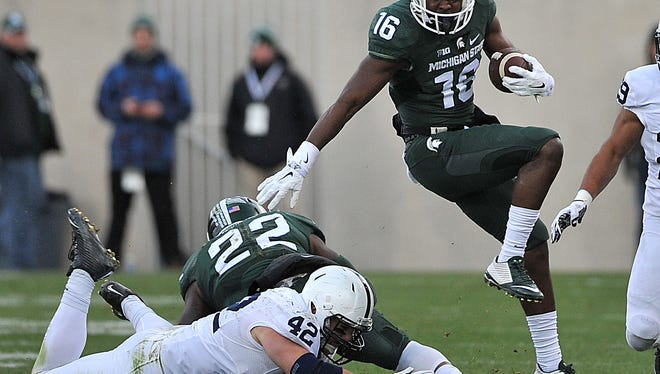 MSU's Aaron Burbridge leaps over a tackler on his way to a first down as MSU hosts Penn State Saturday.