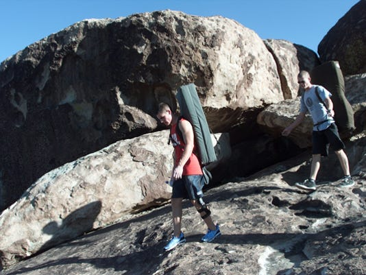 Steven Romero, left, and James Robertson hike back to their cars after climbing boulders on the north mountain at Hueco Tanks State Park.