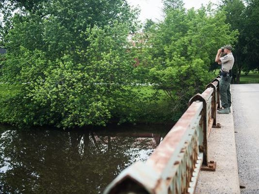 An officer with the Pennsylvania Fish and Boat Commission scans Conewago Creek on Wednesday.