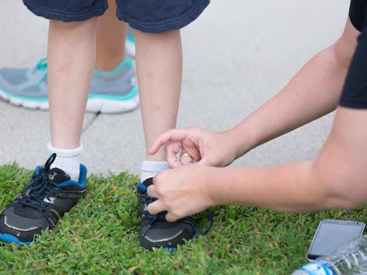 A mother ties her son's shoelaces while waiting for the bus on Hanover Public School District's first day of school.