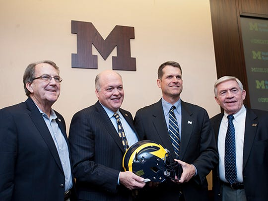 Lloyd Carr, Jim Hackett, Jim Harbaugh and Gary Moeller pose for photos Tuesday.