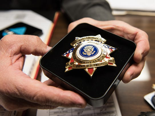 Wicomico County Sheriff Mike Lewis holds a badge created